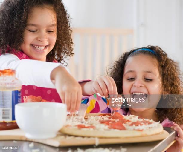 Hispanic sisters making pizza