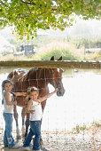 Hispanic sisters petting horse