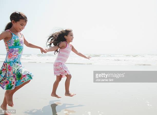 Hispanic sisters playing at beach