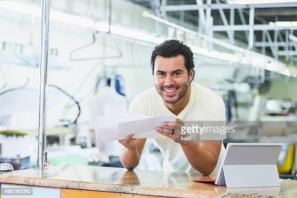 Hispanic petite entreprise propriétaire, teinturier payant les factures
