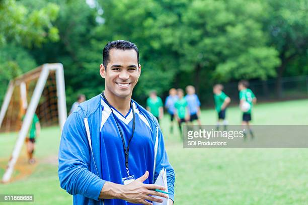 Hispanic soccer coach smiles confidently before game