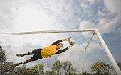 Hispanic soccer goalie catching soccer ball in air