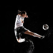 Hispanic soccer player splashing in water