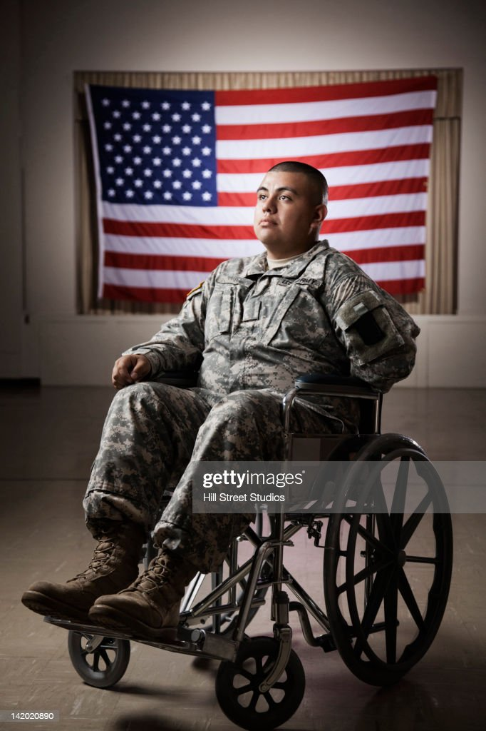 Hispanic soldier in wheelchair near American flag