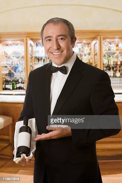 Hispanic sommelier displaying a bottle of wine
