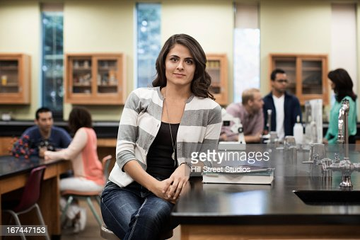 Hispanic student sitting at desk in lab classroom : Stock Photo