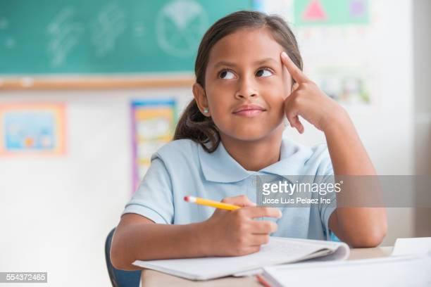 Hispanic student thinking in classroom