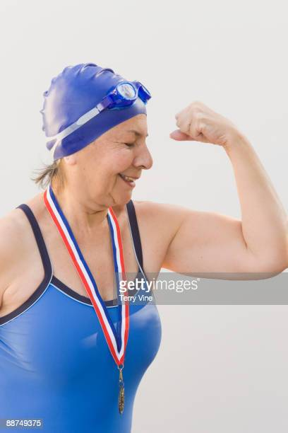 Hispanic swimmer wearing medal and showing muscles