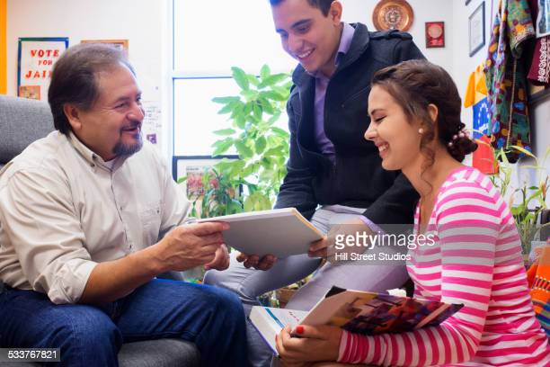 Hispanic teacher and students working together in office