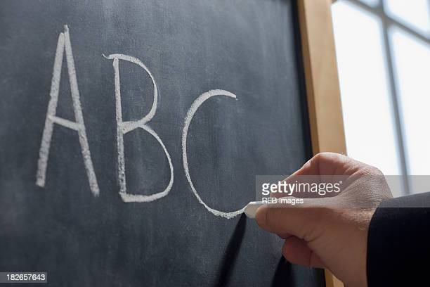 Hispanic teacher writing 'ABC' on chalkboard