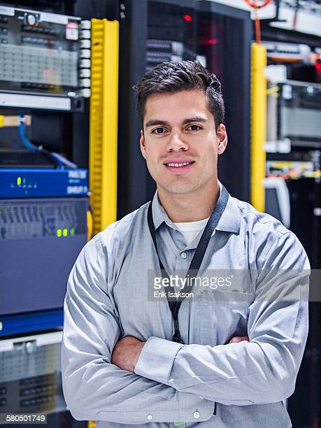 Hispanic technician smiling in server room