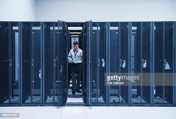 Hispanic technician working in server room