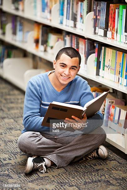 Hispanic teenage boy reading in library