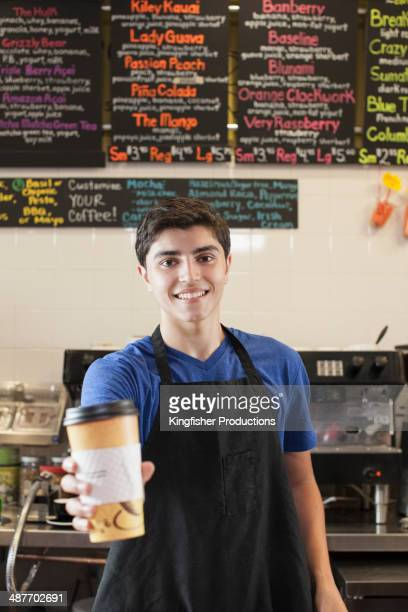 Hispanic teenage boy serving coffee in cafe