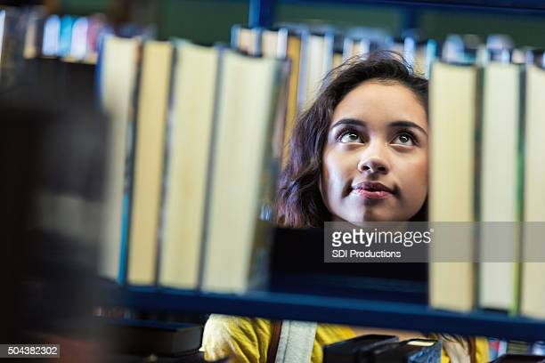 Hispanic teenage college student searching for books in library