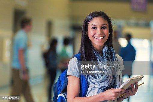 Hispanic teenage female high school student smiling in hallway
