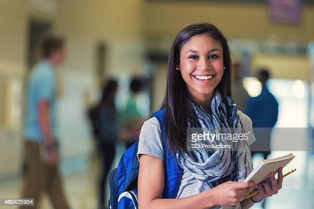 Jeune femme hispanique collège étudiant souriant dans le couloir