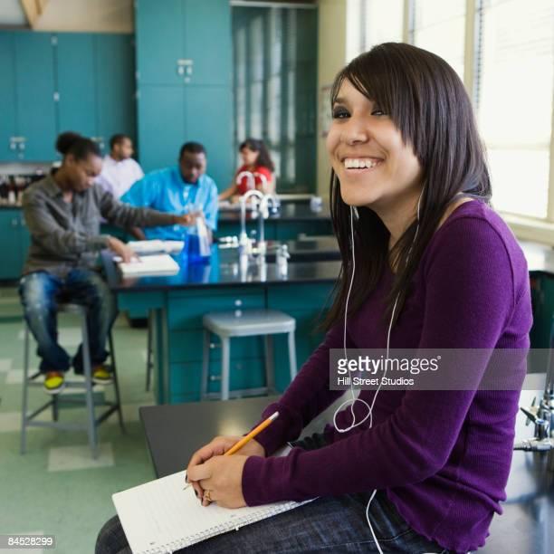 Hispanic teenage girl listening to mp3 player in chemistry lab