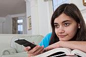 Hispanic teenage girl watching television