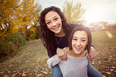 Cute hispanic teenage girls playing together outdoors during a warm fall day. Sun flare in the background