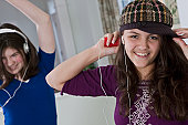 Hispanic teenage girls listening to an MP3 player and dancing with her friend