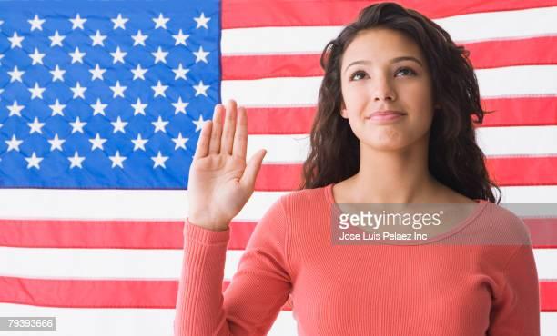 Hispanic teenaged girl in front of American flag