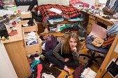 Hispanic teenaged girl sitting in messy bedroom