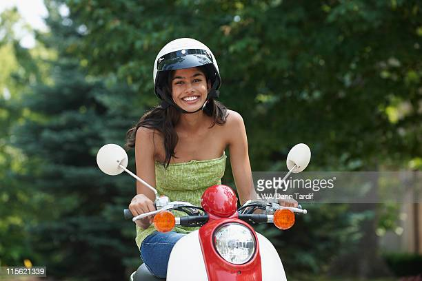 Hispanic teenager riding scooter