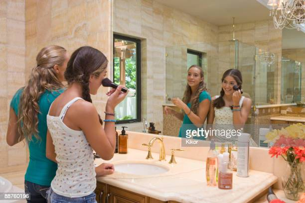 Hispanic teenagers applying makeup in bathroom mirror