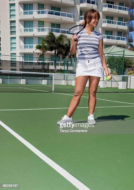 Hispanic tennis player holding racket and ball