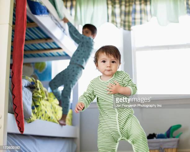 Hispanic toddler standing in bedroom