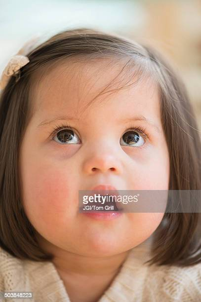 Hispanic toddler with Down syndrome looking up