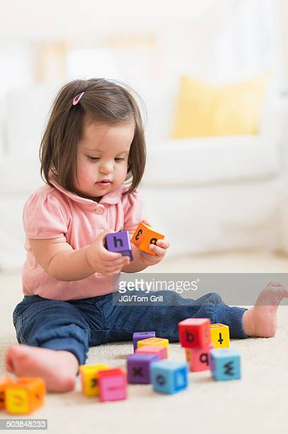 Hispanic toddler with Down syndrome playing with blocks
