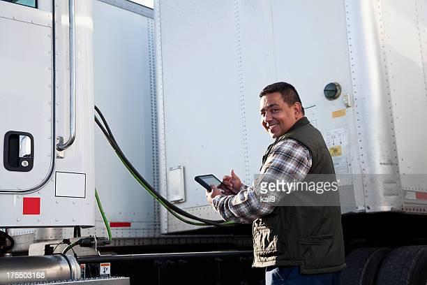 Hispanic LKW-Fahrer mit digitalen tablet