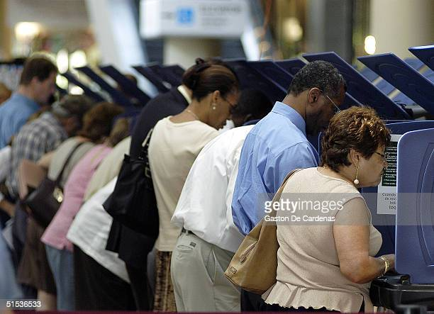 Hispanic voters go to the polls for early voting at the MiamiDade Government Center on October 21 2004 in Miami Florida Early voting began this week...