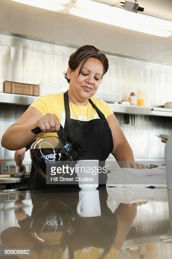 Hispanic waitress pouring coffee in diner