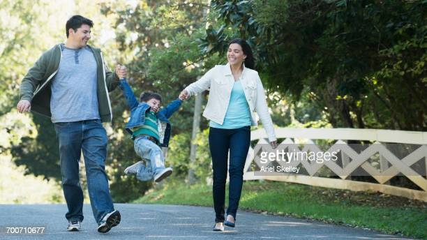 Hispanic walking in park swinging son by arms