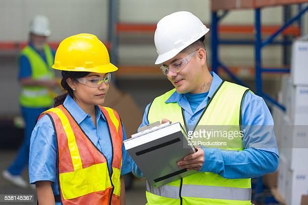 Hispanic warehouse supervisor explaining order to female employee