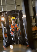 Hispanic warehouse worker driving forklift