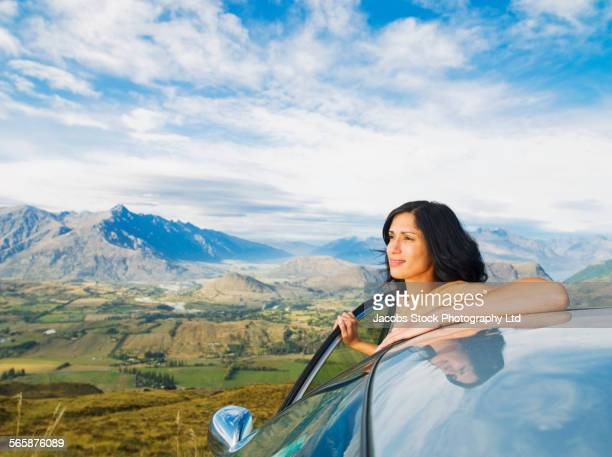 Hispanic woman admiring view from remote hilltop, Queenstown, South Island, New Zealand,