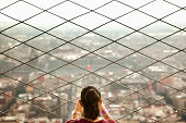 Hispanic woman admiring view from skyscraper