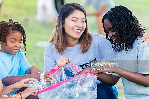 Hispanic woman and African American girls help with community cleanup