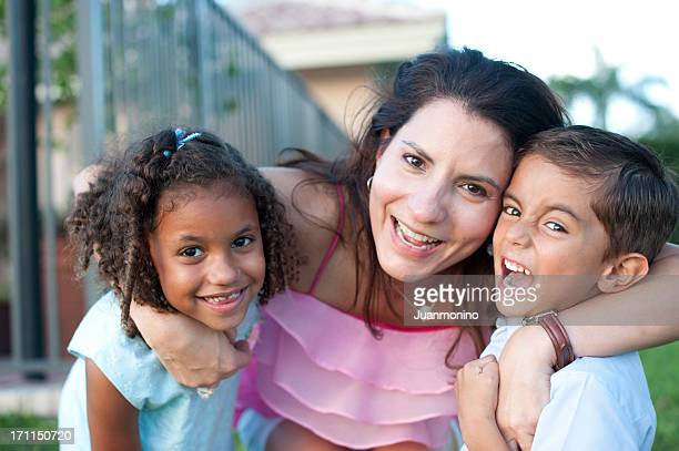 Hispanic woman and two kids happily looking at the camera