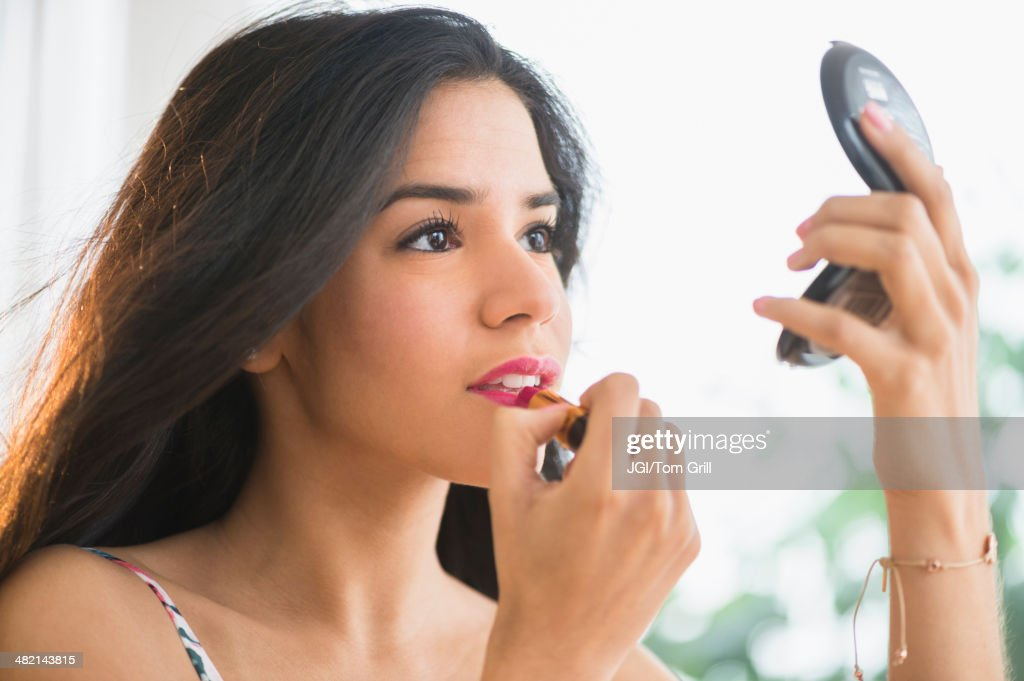 Hispanic woman applying lipstick in compact mirror