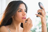 Hispanic woman applying lipstick in compact mirror