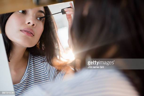 Hispanic woman applying mascara in mirror