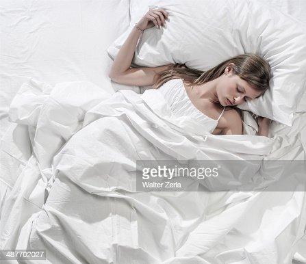 Hispanic woman asleep in bed