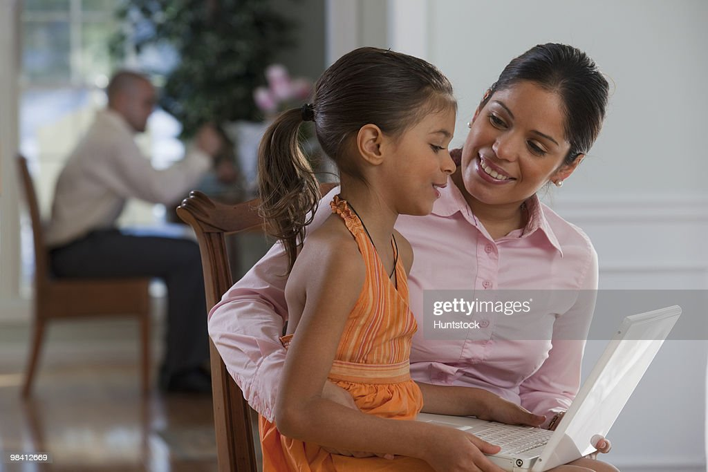 Hispanic woman assisting her daughter in using laptop