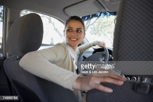 Hispanic woman backing up car