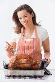 Hispanic woman basting turkey